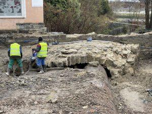 Zbliżenie na kamienną konstrukcję demontowanego przepustu. Dwóch pracowników skuwa jego elementy