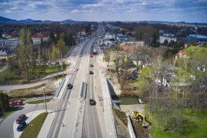 Zdjęcie z drona w osi ul. Cieszyńckiej w kierunku centrum Wapienicy z widokiem na nowy most na potoku Wapienica. Koparka umacnia jego nasyp