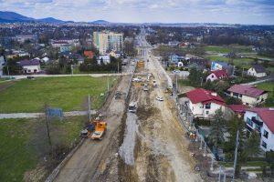 Widok na ulicę Cieszyńską na wysokości skrzyżowania z ul. Krzywą w kierunku centrum Wapienicy. Koncentracja sprzętu i ludzi pracujących nad utwardzeniem podbudowy ulicy