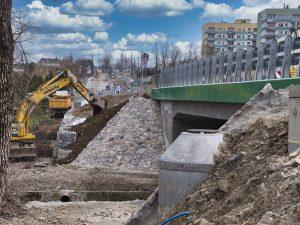 Koparka pracująca przy nasypie nowego mostu na potoku Wapienica