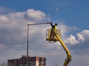 Instalator pracujący na wysięgniku montuje oprawę oświetlenia ulicznego
