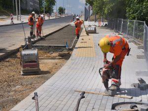 Pracownicy drogowi podczas prac brukarskich i układania warstwy betonu w powstającej zatoce autobusowej na odcinku trzecim rozbudowywanej ul. Cieszyńskiej