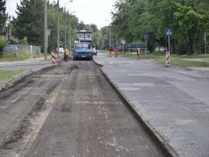 Zdjęcie wykonane w osi ulicy Czesława Tańskiego. W pierwszym planie wyfrezowana zniszczony pas asfaltu. W oddali pojazdy drogowców, wokół których pracują robotnicy