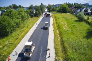 Widok z drona. Prace asfaltowe na drodze serwisowej w kierunku ul. Tańskiego. Dwa walce drogowe walcują świeży asfalt, za nimi drogowcy obsługują rozściełacze kładące ścieralną warstwę asfaltu