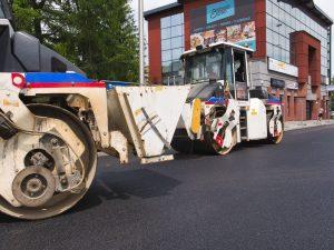Dwa mijające się walce drogowe podczas walcowania świeżo położonego asfaltu na ul. Cieszyńskiej