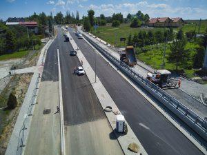 Ujęcie z drona na ul. Cieszyńską w rejonie skrzyżowania z ul. Krzywą. Południowa jezdnia serwisowa podczas układania podbudowy z kruszywa. Pozostałe jezdnie pokryte wiążącymi warstwami asfaltu