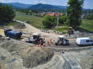 Zdjęcie z drona w zbliżeniu na ekipę drogowców obsługujących rozściełacz na nowym rondzie w rejonie dawnych zakładów szybowcowych