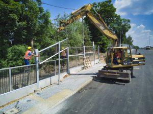 Budowlańcy przy pomocy dźwigu instalują przezroczysty panel dźwiękochłonny do powstającej konstrukcji bariery wzdłuż trzeciego odcinka rozbudowywanej ul. Cieszyńskiej