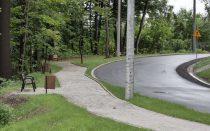 Zakręt na ul. Falistej, nowy chodnik z zatoczkami oraz ławkami. Wzdłuż przeciwległej krawędzi ulicy nowe odwodnienie.